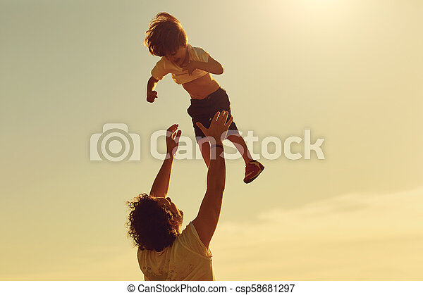 Father and child playing in nature at sunset. - csp58681297