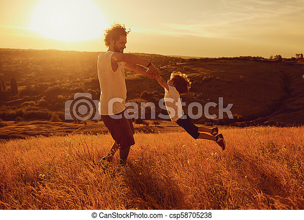 Father and child playing in nature at sunset. - csp58705238