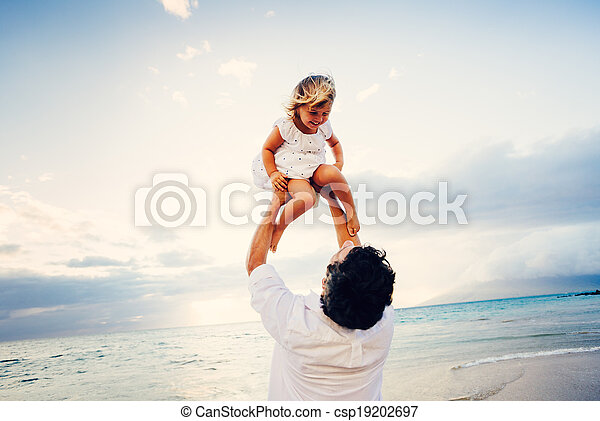Father and Daughter Playing Together at the Beach at Sunset - csp19202697