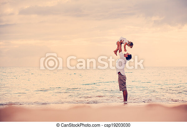 Father and Daughter Playing Together at the Beach at Sunset - csp19203030