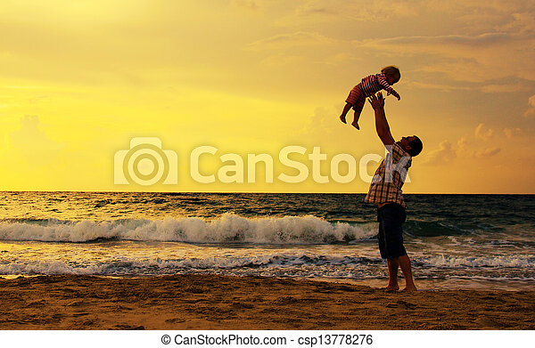 father and daughter playing together on the beach at sunset - csp13778276