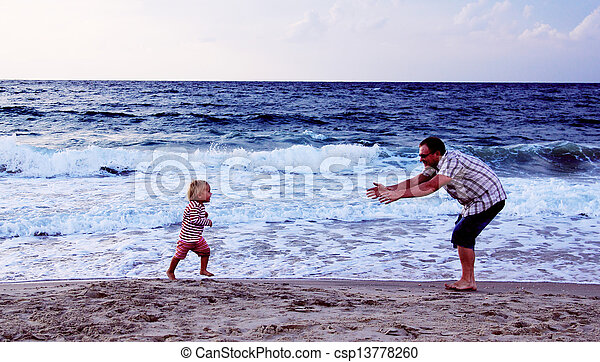 father and daughter playing together on the beach at sunset - csp13778260