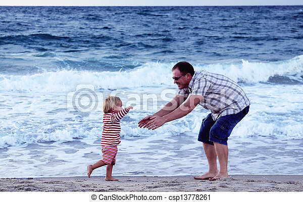 father and daughter playing together on the beach at sunset - csp13778261
