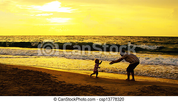 father and daughter playing together on the beach at sunset - csp13778320