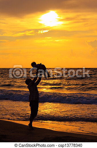 father and daughter playing together on the beach at sunset - csp13778340