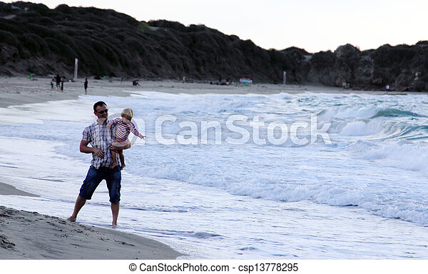 father and daughter playing together on the beach at sunset - csp13778295