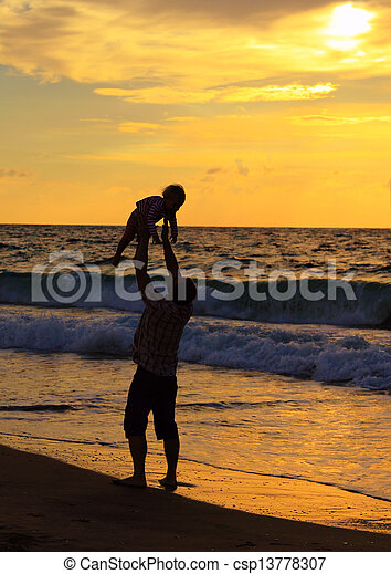 father and daughter playing together on the beach at sunset - csp13778307