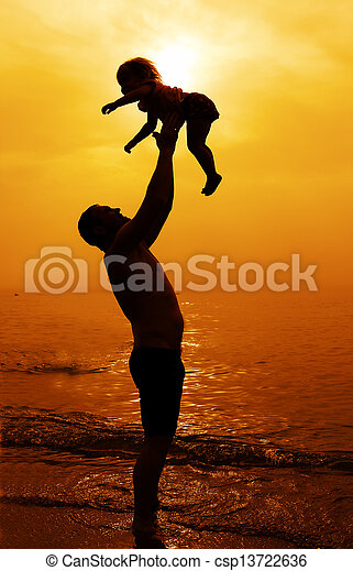 father and daughter playing together on the beach at sunset - csp13722636