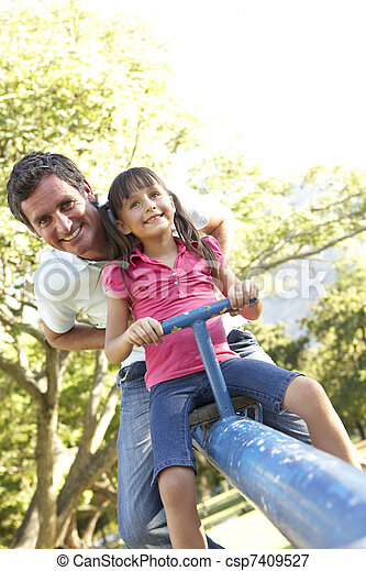 Father And Daughter Riding On See Saw In Playground - csp7409527