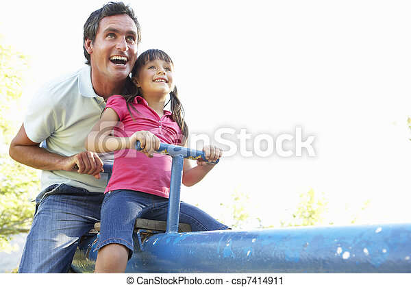 Father And Daughter Riding On See Saw In Playground - csp7414911