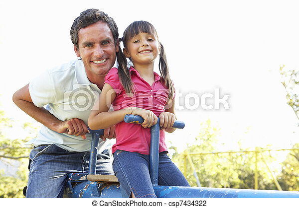 Father And Daughter Riding On See Saw In Playground - csp7434322