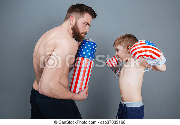 Father and son in boxing gloves training using punching bag - csp37033168