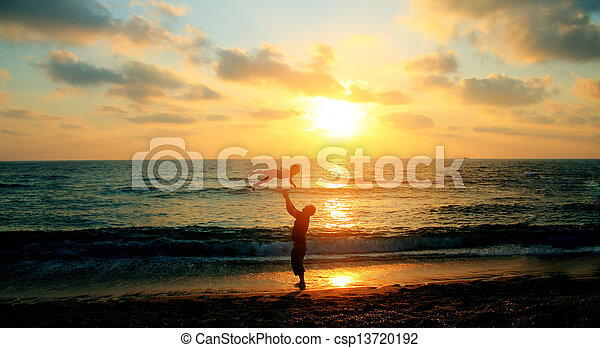 father and son on a walk by the sea at sunset - csp13720192