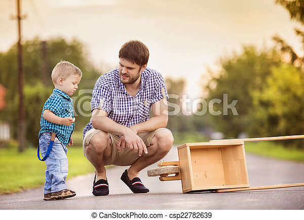 Father and son on road with wheelbarrow - csp22782639