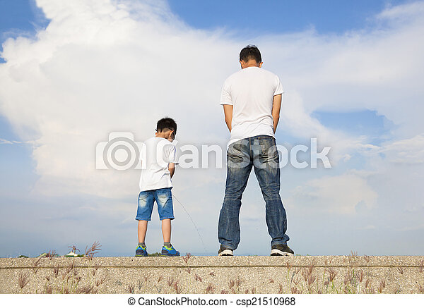 1bf9d929c father and son standing on a stone platform and pee together - csp21510968