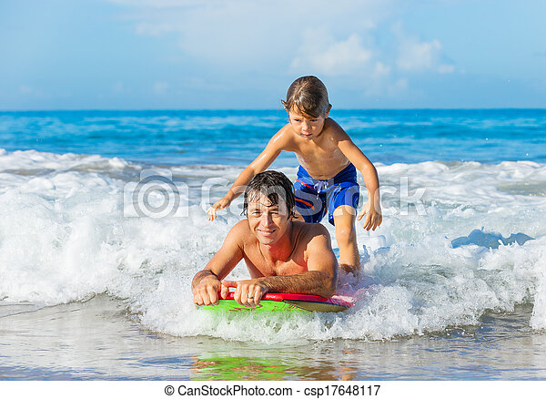 Father and Son Surfing Tandem Together Catching Ocean Wave, Carefree happy fun smiling lifestyle - csp17648117