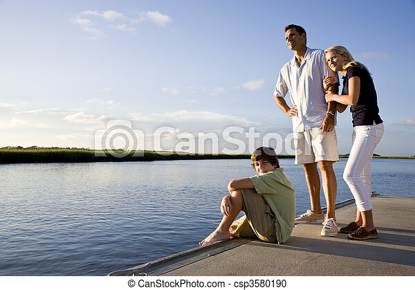 Father and teenage children on dock by water - csp3580190