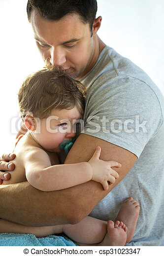 Father comforts son. Sleepy baby boy cuddling his father.