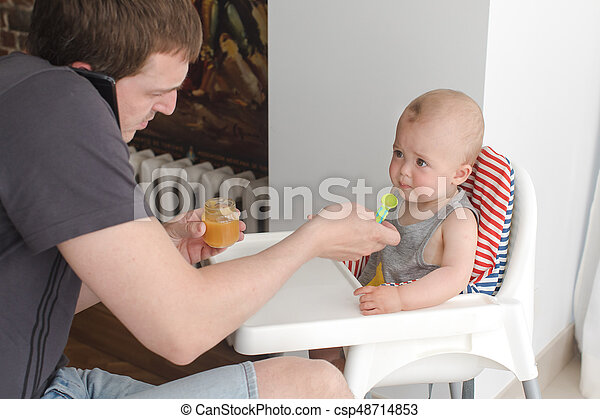 Father feeding infant son while talking phone - csp48714853