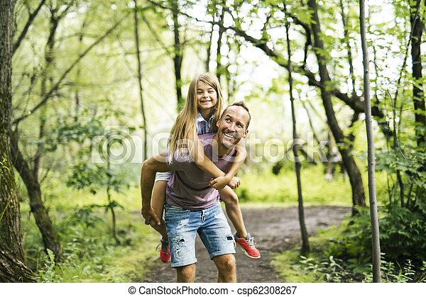 Father giving his daughter a piggyback ride, having fun - csp62308267