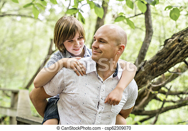 Father giving his son a piggyback ride, having fun - csp62309070