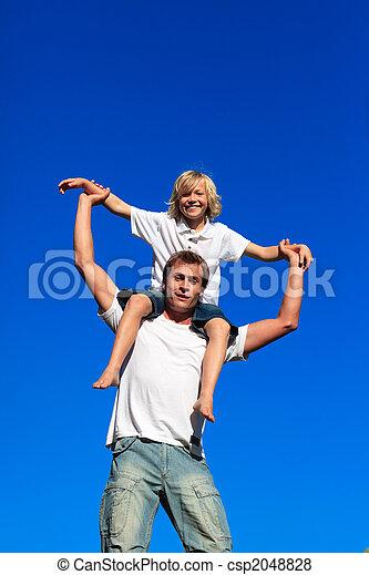 Father giving his son a piggyback ride - csp2048828