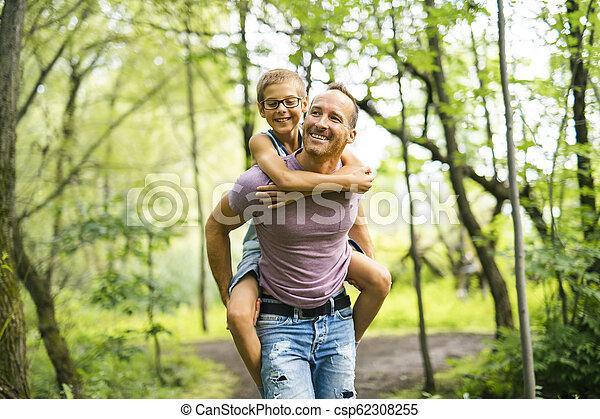 Father giving his son a piggyback ride, having fun - csp62308255