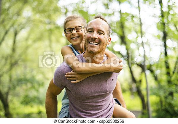 Father giving his son a piggyback ride, having fun - csp62308256