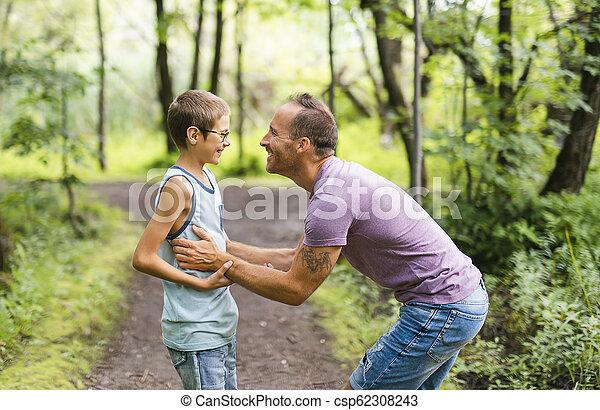 Father giving his son a piggyback ride, having fun - csp62308243