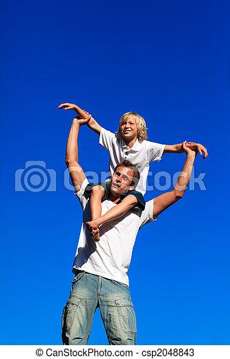 Father giving his son a piggyback ride - csp2048843