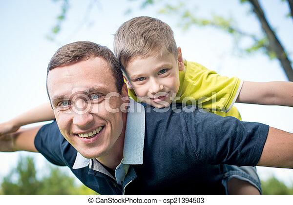 Father giving piggyback ride to his son - csp21394503