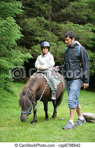 Father helping his daughter ride a pony - csp8798642