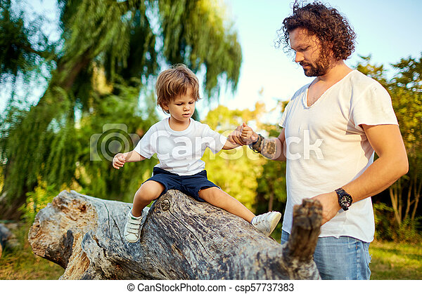 Father playing with his son in the park. - csp57737383
