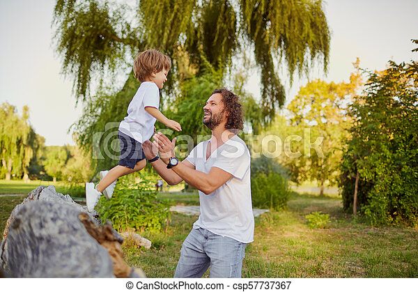 Father playing with his son in the park. - csp57737367