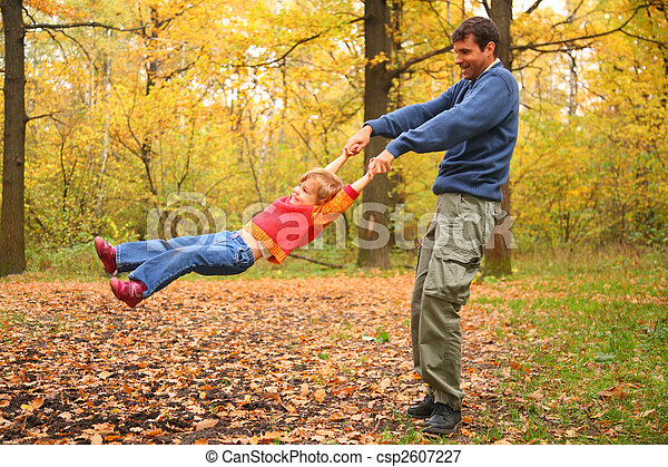 Father rotates child for hands in wood - csp2607227