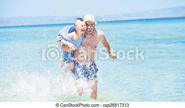 father son splashes running sea - csp28817313