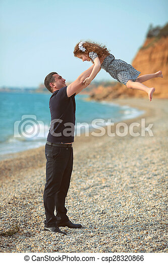 Father toss up daughter playing together on the beach carefree happy fun smiling lifestyle - csp28320866