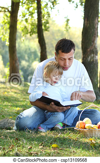 father with a young daughter read the Bible in nature - csp13109568