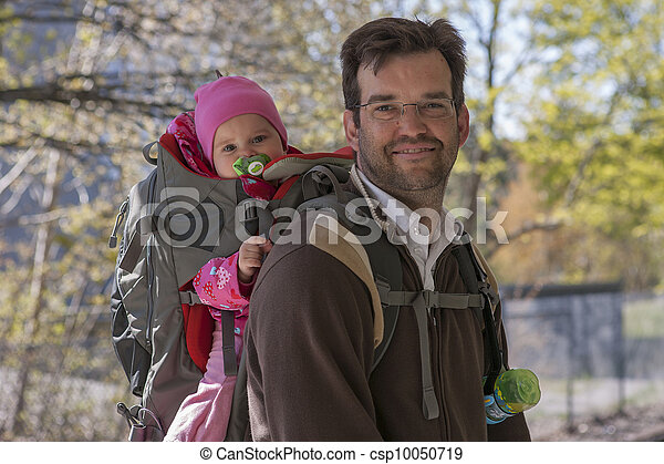 Father with daughter in backpack carrier - csp10050719