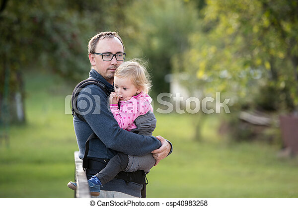 Father with his daughter in baby carrier. Green nature. - csp40983258