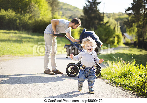 Father with little son and baby daughter in stroller. Sunny park. - csp48099472