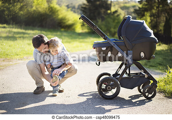 Father with little son and baby daughter in stroller. Sunny park. - csp48099475