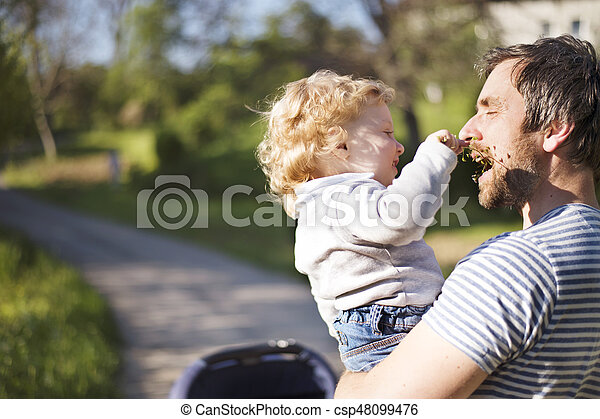 Father with little son and baby daughter in stroller. Sunny park. - csp48099476