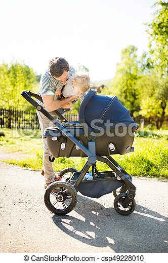 Father with little son and baby daughter in stroller. Sunny park - csp49228010