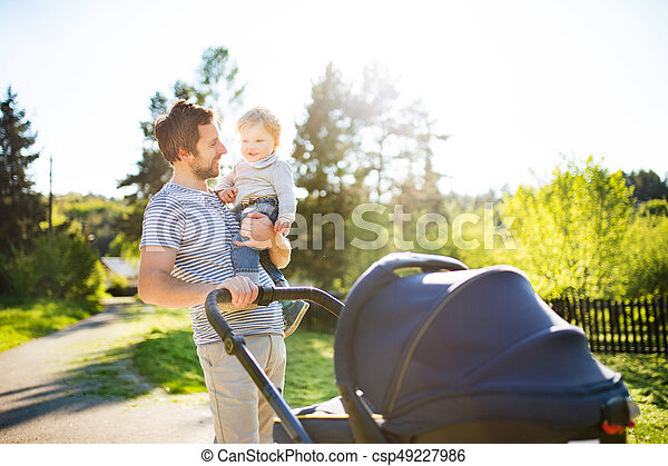 Father with little son and baby daughter in stroller. Sunny park - csp49227986