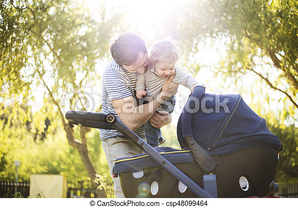 Father with little son and baby daughter in stroller. Sunny park. - csp48099464