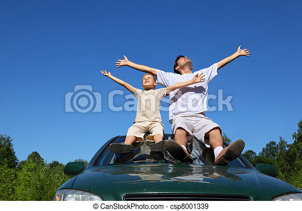 Father with  son sit on  roof of car, lift  person in sky and widely place hands - csp8001339