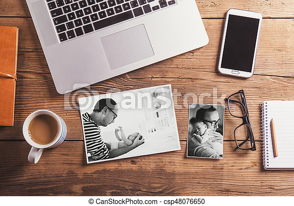 Fathers day concept. Black-and-white photos of father and son. Office desk with various things. Studio shot on wooden background.