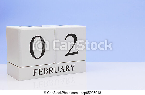 February 02st. Day 02 of month, daily calendar on white table with reflection, with light blue background. Winter time, empty space for text - csp65928918