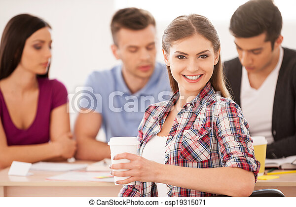 Feeling confident about her final exam. Four cheerful students sitting together at the desk and studying while beautiful woman looking over shoulder and smiling - csp19315071